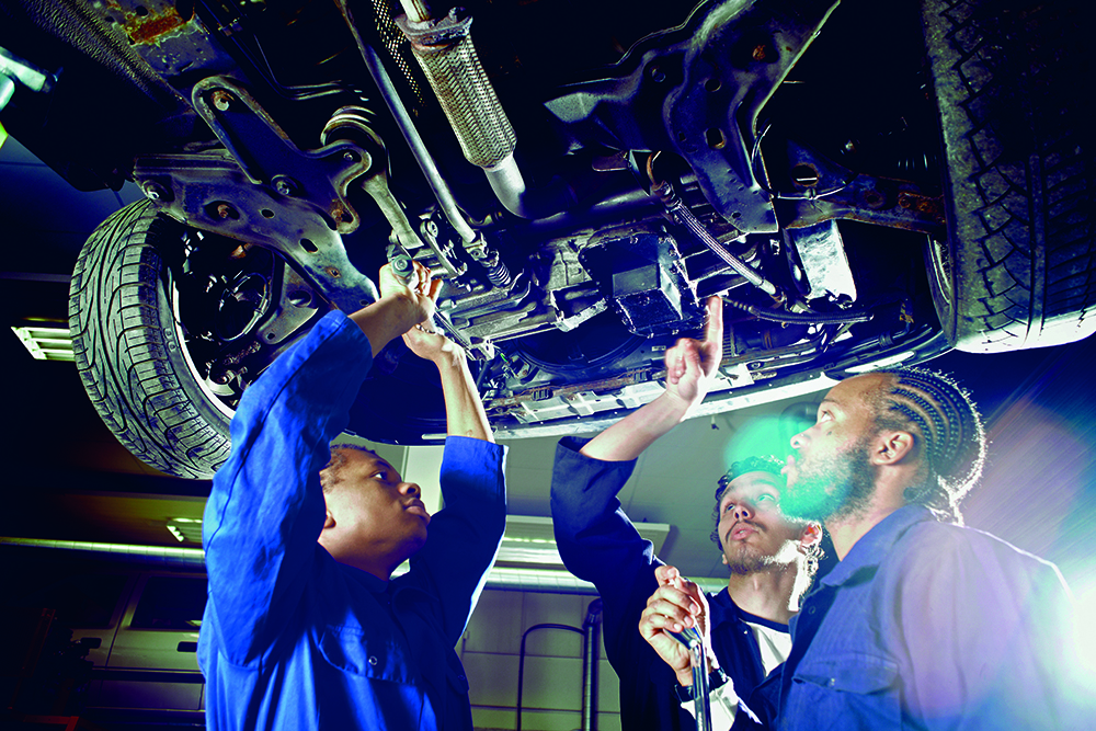 Three college students looking up at car in garage workshop